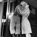 A soldier kisses his girl goodbye - ready to board a train..