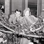 Marlene Dietrich and Carry Grant, two of Hollywood's brightest stars, are pictured posing amid the posifs in the garden of the S.S. Normandie as they arrived from Europe today, just in time for Thanksgiving Dinner.