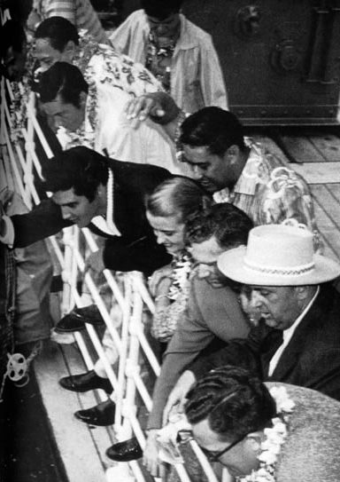 Presley and party waving to fans upon his arrival aboard the SS Matsonia in Honolulu...