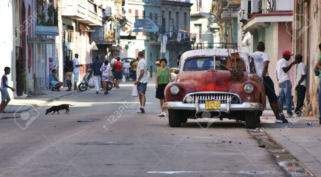 13760951-Central-Havana-Street-scene-with-old-american-car-parked-on-the-side-with-wooden-boat-on-it-few-peop-Stock-Photo
